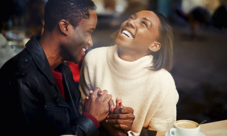 Young man and woman sitting close together in coffee shop, their hands clasped, both smiling, woman's head tilted upward in glee
